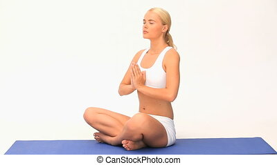 Pretty woman doing yoga against a white background