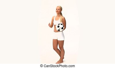 Pretty blonde woman playing with a soccer ball isolated on a...