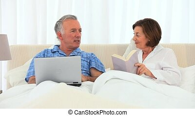 Retired couple talking in the bed