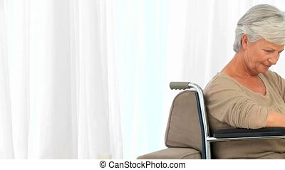 Senior woman in a wheelchair thinking in the living room