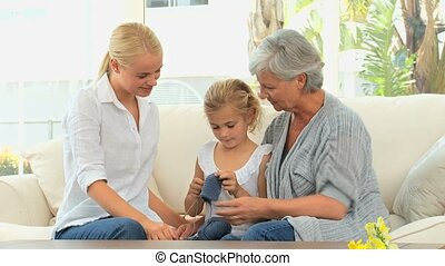 Girl knitting with her mother and Grandmother on the sofa
