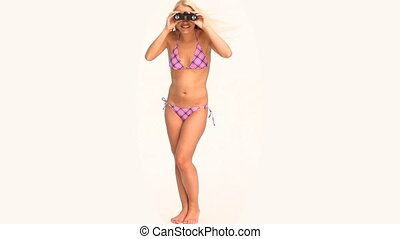 Woman in swimsuit looking for someone with a pair of binoculars