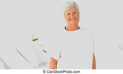 Retired woman looking at the camera in a white living room