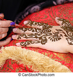 Henna art - A womans hand being decorated with henna by an...