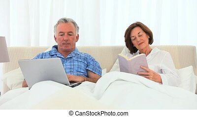 Elderly man working on his computer while his wife is reading