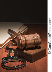 Gavel and Handcuffs - Handcuffs and a wooden gavel in front...