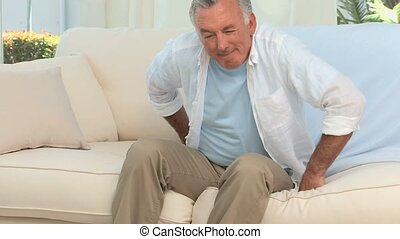 Retired man having a back pain on his sofa