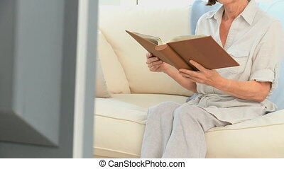 Senior woman reading a book on her sofa
