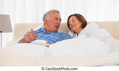 Elderly couple watching tv in the bed