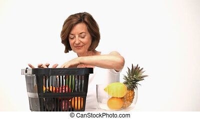 Senior woman putting fruit into a bowl isolated on a white...