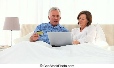 Elderly couple using a credit card on the internet on a bed