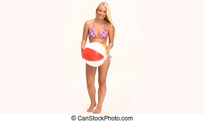 Woman in a swimsuit playing with a ball against a white...