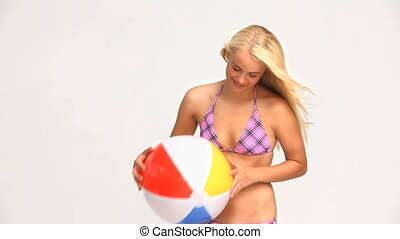 Woman playing with a ball isolated on a white background