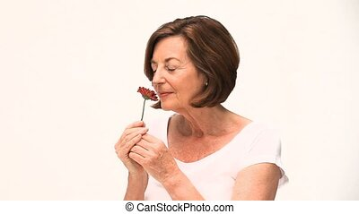 A woman smelling a flower against a white background