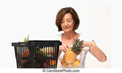 Mature woman putting fruit into a bowl isolated on a white...