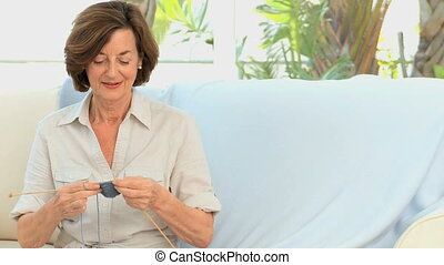Elderly woman knitting in the living room