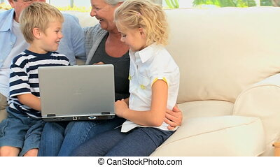 Family laughing in front of a computer in the living room