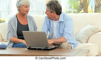 Retired couple talking in front of a computer in the living...