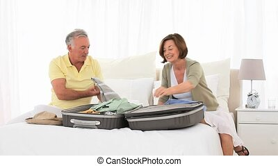 Mature couple leaving for vacacion and packing - Mature...