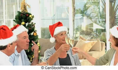 Seniors friends celebrating Christmas in the living room
