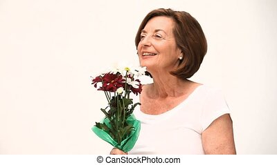 Senior woman smelling a flower against a white background