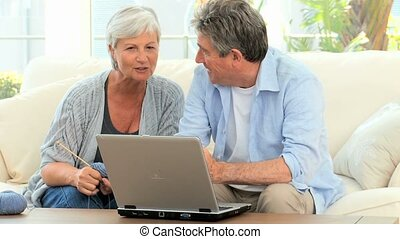 Mature couple looking at the laptop