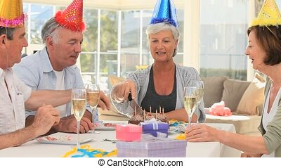 Seniors friends celebrating a birthday in the dinning room