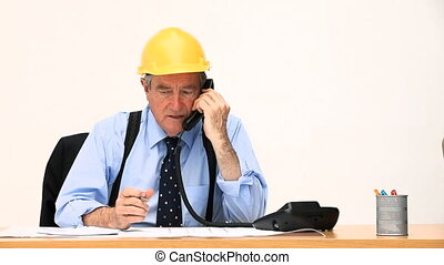 Active retired man working on a building project at his desk