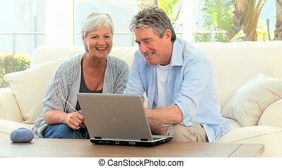 Senior couple looking at a computer in the living room