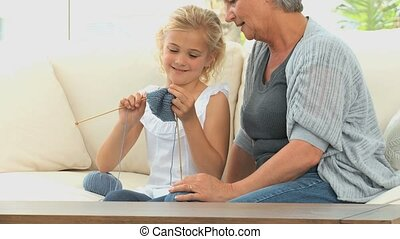 Gril learning to knit with her grand mother in the living...