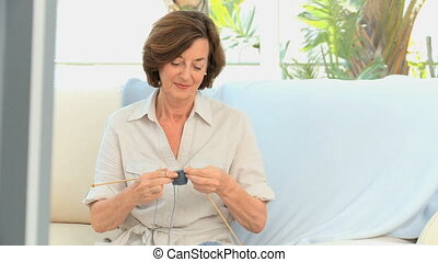Senior woman knitting on a sofa