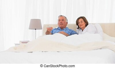 Retired couple wathing tv in the bed