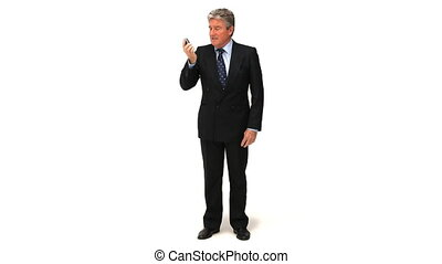 A businessman talking on the phone against a white...