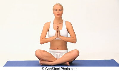 Blond woman doing yoga against a white background