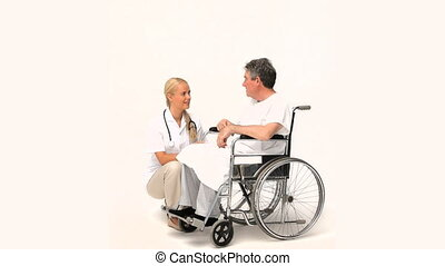 Man in a wheelchair talking to his nurse isolated on a white...