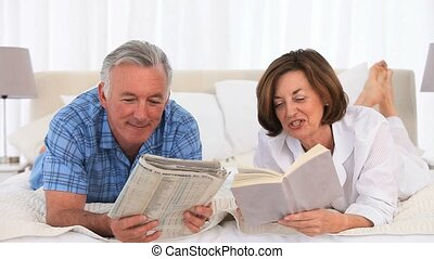 Retired couple reading on the bed