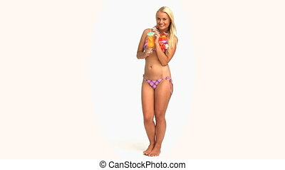 Blond woman in a swimsuit drinking a cocktail isolated on a...