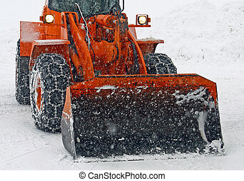 orange snow plow clears the streets during a snow storm