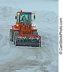 orange snow plow clears the streets during a snow storm in...