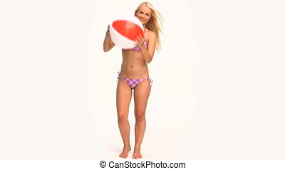 Woman in swimsuit playing with a ball against a white...
