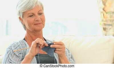 Mature woman knitting in the living room