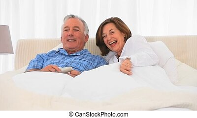 Retired couple watching tv in the bedroom