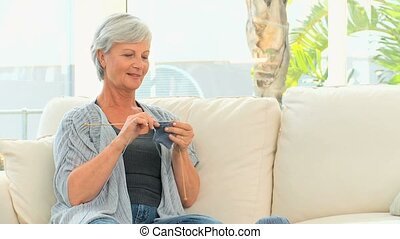 Retired woman knitting in the living room