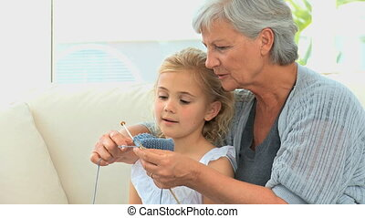 Grandmother with her grand daughter knitting at home