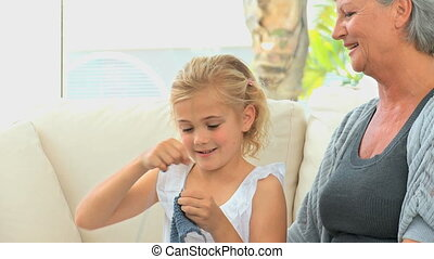 Grandmother teaching her grand daughter how to knit -...