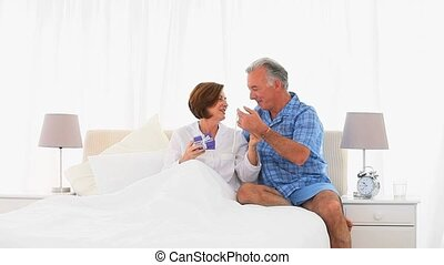 Senior man offering a present to his wife in the living room