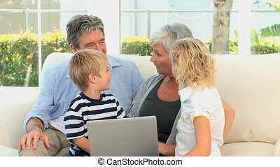 Family in front of a computer talking on a sofa