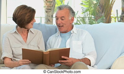 Aged couple looking at a photos album in the living room
