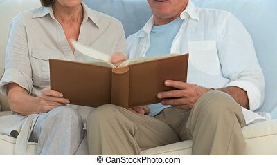 Retired couple looking at a photo album on a sofa