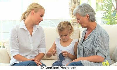 Girl learning to knit with her mother and Grandmother